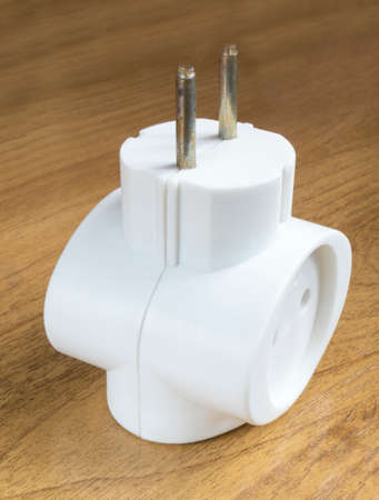 distributor: White electric network distributor rests upon brown table Stock Photo