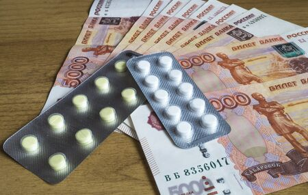 medical bills: Money bills are with medical tablet to rest upon wooden table Stock Photo