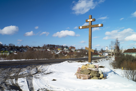 cross roads: Wooden cross beside roads on background blue sky at the beginning initially city Mstera,Russia Stock Photo