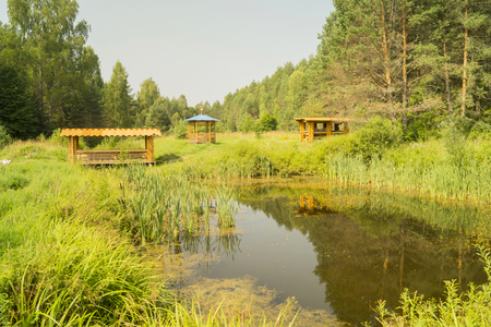 summerhouse: Wooden summerhouse on edge of a forest wood near by small lake Stock Photo
