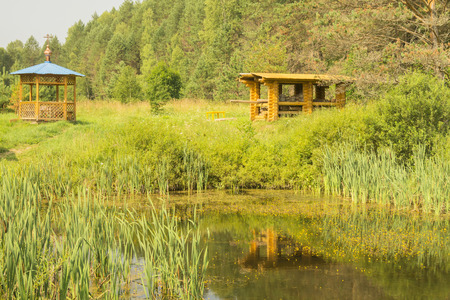 the furlough: Wooden summerhouse on edge of a forest wood near by small lake Stock Photo