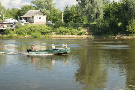 the furlough: Vyazniki,Russia-August 1,2016: Man and woman with dog sail on boat on river 1 August 2016 in city Vyazniki,Russia