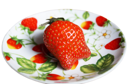 zooming: Red berry of the strawberry on colour plate insulated on white background Stock Photo
