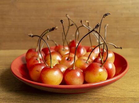 Red ripe sweet cherries on plate on wooden table with focus on foregrounds