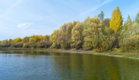 Autumn landscape with river at autumn length of time on background blue sky