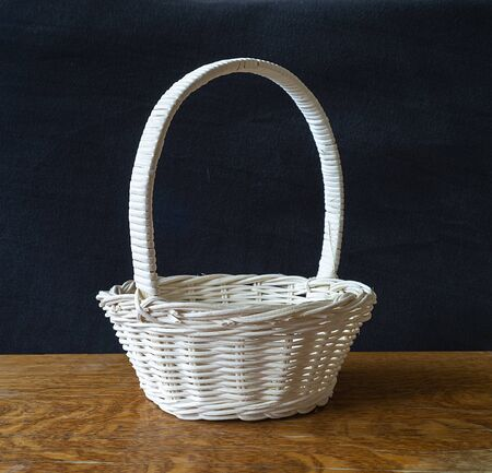 Blanching basket braided from twig on dark background cost(stand)s on wooden table