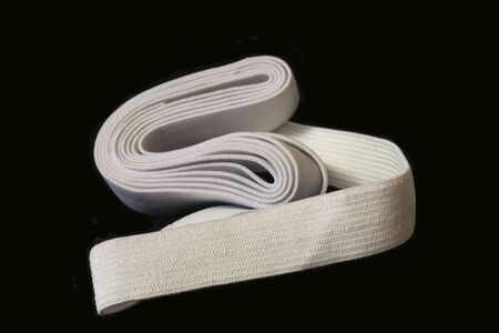 Blanching rubber-band fabric tape for needlework of the cloth insulated on black background
