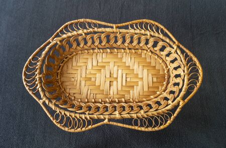 The Braided basket from twig of the osier for fruit. The Beautiful decorative kitchen utensil on dark background. Type overhand