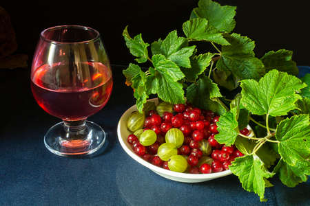 The Red currant with gooseberry in white plate on background green sheet. Still life with berry and juice on black