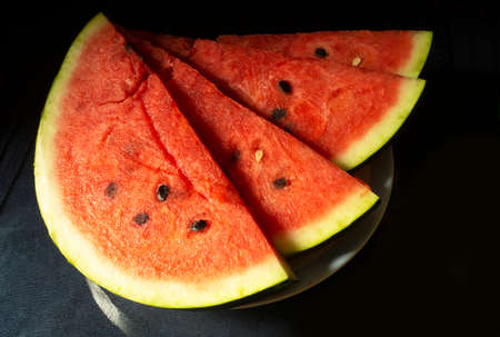 The Ripe watermelon in plate on black background. The Slices fruit with red pulp. Sweet products of the feeding
