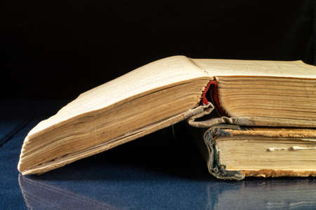 Aging book rests upon glass table with reflection. Subjects on black background close-up Imagens