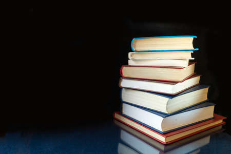 The Stack of the books rests upon turn blue the table with reflection. Subjects on black background close-up