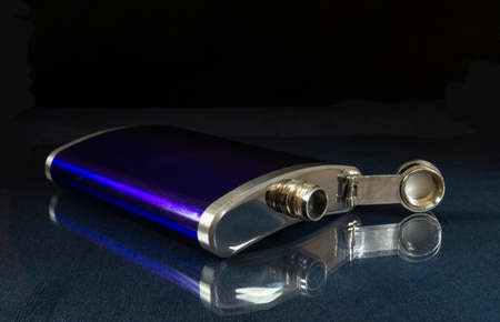 The Metallic flask for alcohol on table with reflection. Brilliant subject on black background
