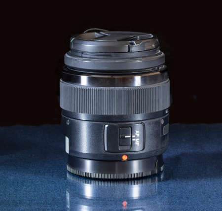 The black lens of the camera is lying on a glass table. Photographer's equipment on a black background