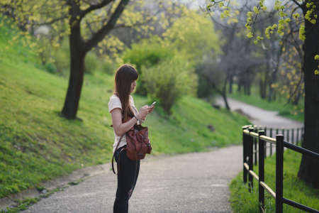 Attractive young woman having fun outside in park . Caucasian girl with long brown writing on her mobile Stock Photo