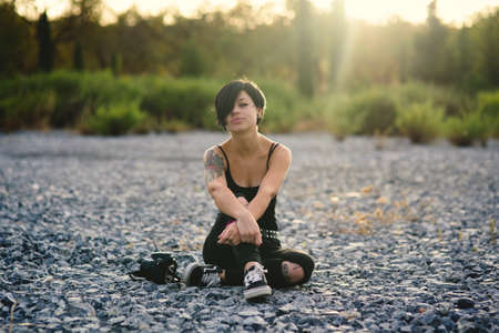 Beautiful young photographer woman wearing black clothes and short haircut sitting on the stone floor outdoors. Caucasian brunette girl thinking relaxed in the countryside.