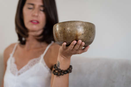 Woman doing yoga with tibetian singing bowl at home Stock fotó
