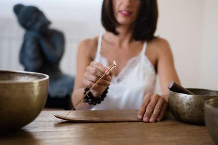 Close up of womans hands burning a incense stick Standard-Bild