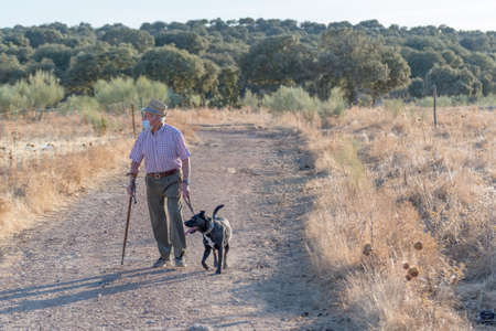 old man with a cane that helps him walk walking with his dog through the streets of his quiet town