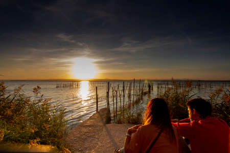 Love concept. Unidentified wedding couple watch the sunset sitting next to the