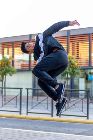Active Latino young man jumping in action. Extreme sport activity, parkour outdoor free running or healthy lifestyle concept 免版税图像