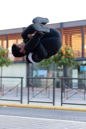 Active Latino young man jumping in action. Extreme sport activity, parkour outdoor free running or healthy lifestyle concept