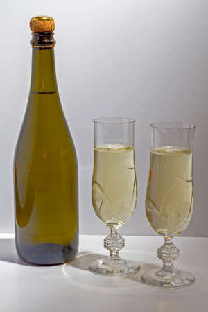 Green bottle with champagne inside and two glasses with champagne on a white background.