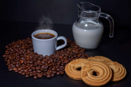 White coffee cup with a coffee drink inside and surrounded by roasted coffee beans of the Robusta variety, a glass jug with milk inside and a donut cake. Breakfast concept