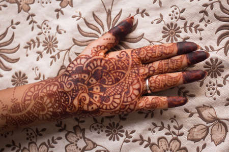 flowery: Indian mehndi henna painting in womans hand at flowery background