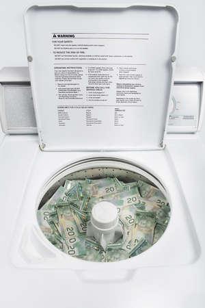 argent: A lot of canadian twenty dollar bills in a white washing machine