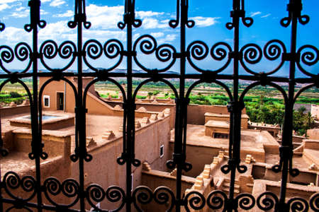 to grate: Moroccan tipical kasbah beyond window grate