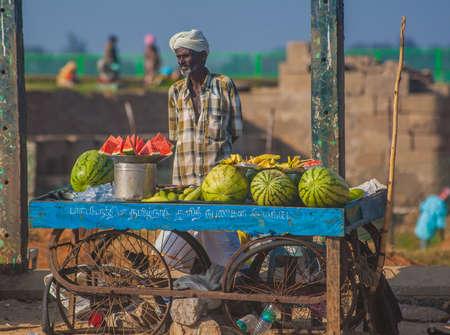 Man selling fresh fruits on the beach in Mamallapuram, Tamil Nadu, India.