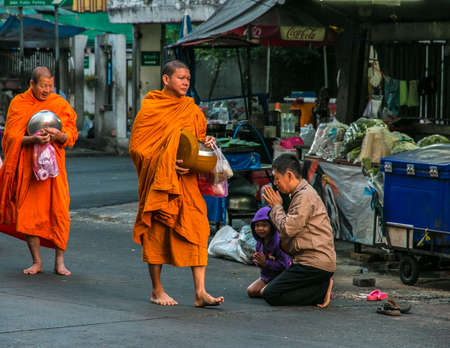 limosna: People giving alms to buddhist monks on the street, Bangkok, Thailand