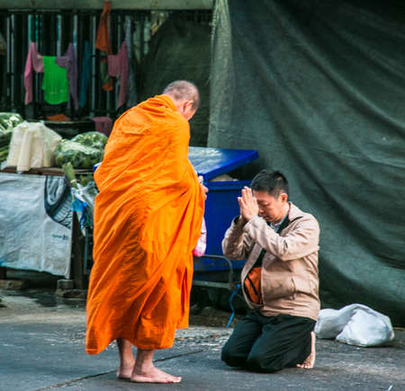 People giving alms to buddhist monks on the street, Bangkok, Thailand