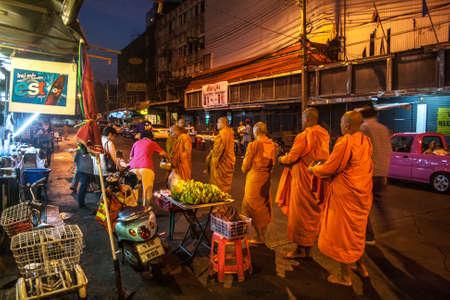 limosna: Las personas que dan limosnas a los monjes budistas en la calle, Bangkok, Tailandia Editorial