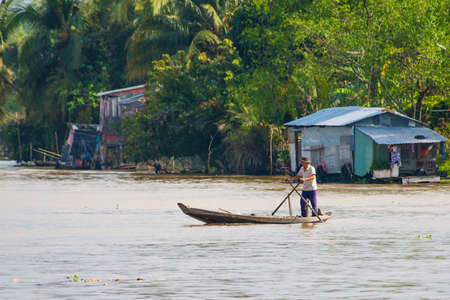 can tho: Unidentified fisherman fishing in a canoe on Mekong river, Can Tho, Vietnam. Editorial