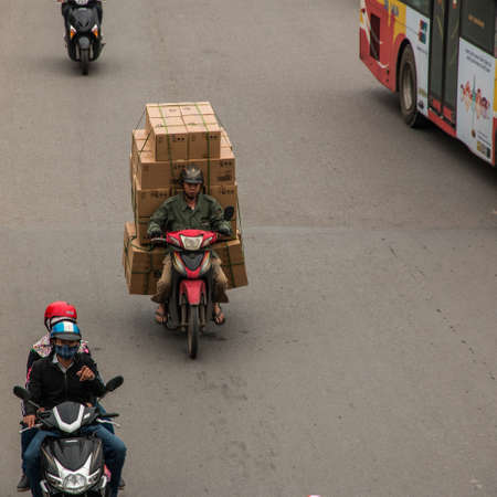 Vietnamese driving a motorbike and transporting a lot of packages. This is a typical Vietnam transport with motorcycle or scooter