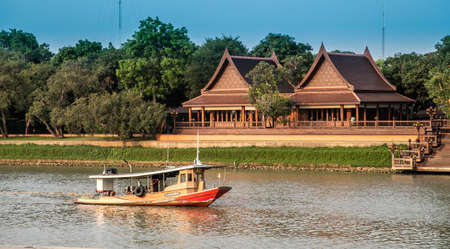 Boat on the Chao Phraya river near Wat Chaiwatthanaram temple in Ayutthaya Historical Park, Thailand