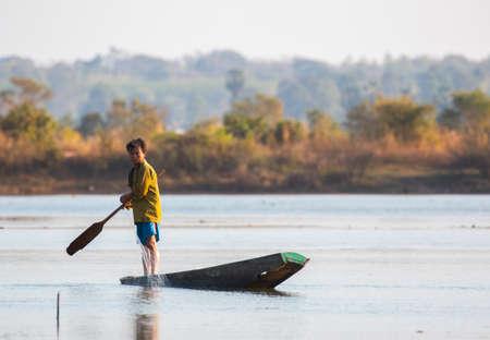 fisherman on canoe in tropical Bungva lake, Laos