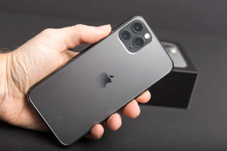 Milan, Italy - December 17, 2019: close up on a handheld brand new Apple iPhone 11 Pro on a black background.