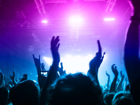 Front view of a concert stage with concert crowd silhouettes clapping and raising hands to the band show