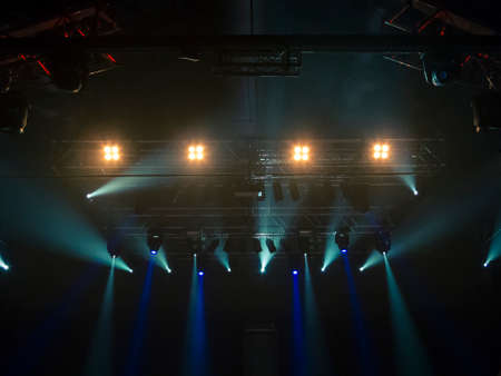 Photo of a concert hall with people silhouettes clapping in front of a big stage lit by spotlights. Shot is taken from concert crowd point of view.