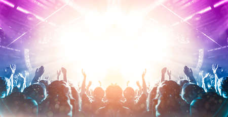 Front view of a concert stage with unrecognizable people silhouettes clapping and raising hands