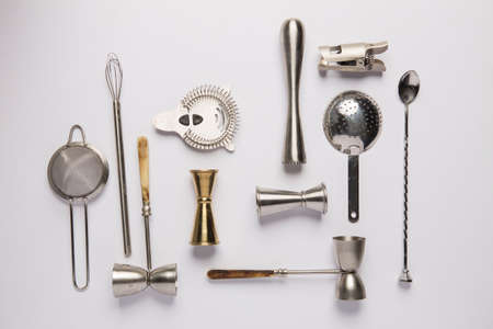 Flat lay composition with bartender iron tools, such as cocktail shaker, jigger, mixing glass, stirring spoon. Background is white.