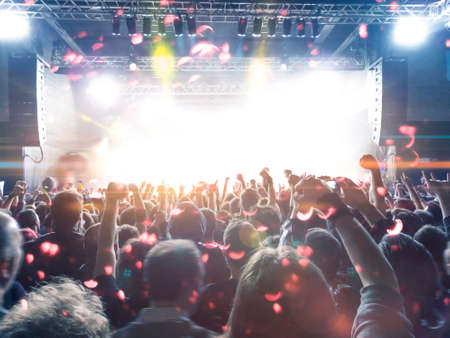 Music festival crowd, concert spectators in front of a bright stage with live music