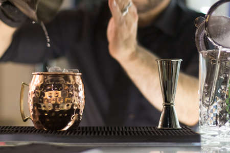 Close up on a copper mug on a bar desk, bartender is pouring a cocktail into it; background is blurred. Stock Photo