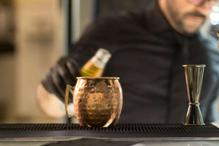 Close up on a copper mug on a bar desk, bartender is pouring a cocktail into it; background is blurred.Close up on a copper mug on a bar desk, bartender is pouring a cocktail into it; background is blurred.