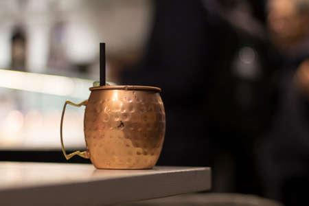 Close up on a copper mug on a bar desk, background is blurred.