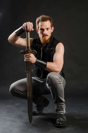 Cosplay portrait of a redhead bearded man holding a two-handed sword. Background is black. Stock Photo