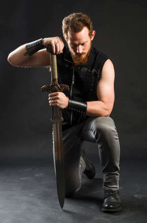 Cosplay portrait of a redhead bearded man holding a two-handed sword. Background is black. Stok Fotoğraf - 147749829